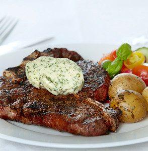 T-bone steak med grillbagte kartofler, urtesmør og græsk salat